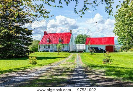 Ile D'Orleans Canada - June 1 2017: Red painted roof house with road in summer landscape French countryside