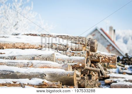 Piled up wood covered in snow,winter scene with cottage in the background