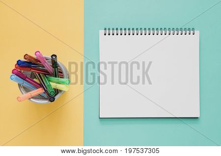 Office Workplace Minimal Concept. Blank Notebook, Color Pen Box On Yellow And Green Turquoise Backgr