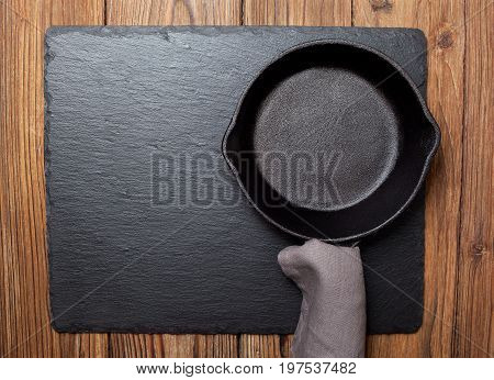 Empty cast-iron frying pan on black slate background (top view)