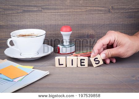lies. Wooden letters on dark background. Office desk