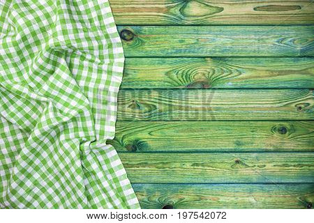 Green checkered tablecloth on wooden table, top view, copy space