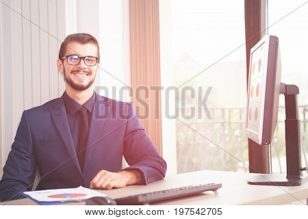 Businessman in suit working at his computer next to a glass window. Image of successful anc competitive entrepreneur at his work place