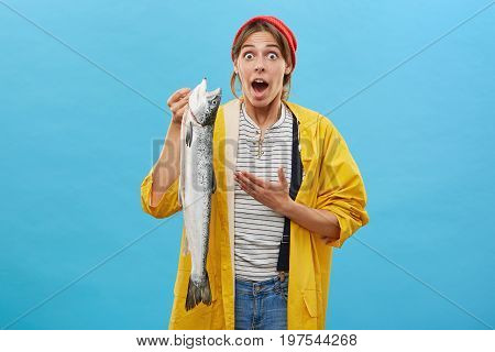 Shocked Female In Casual Clothes Holding Big Long Fish Looking With Jaw Dropped And Bugged Eyes At C