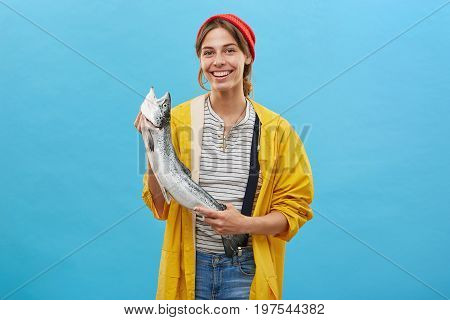 People, Success, Happiness, Fishing Concept. Successful Female Angler Wearing Yellow Anorak And Over