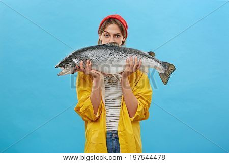 Serious Female Wearing Red Hat And Yellow Anorak Holding Huge Trout Near Her Face Looking With Confi