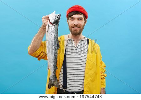 Happy Fisherman With Blue Eyes And Thick Beard Wearing Red Casual Hat And Yellow Anorak Holding In H