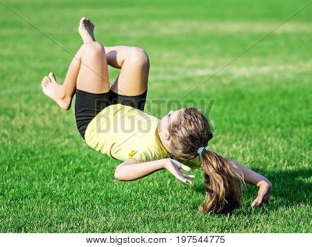 athletic little girl falling on green grass