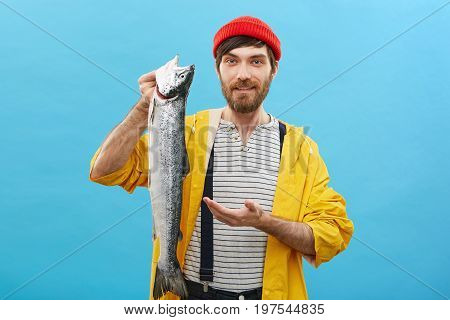 Young Bearded Fishmonger Selling Huge Fish Pointing With Hand At It, Advising Customers To Buy It. P