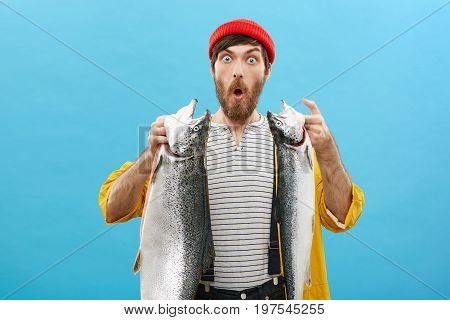 Shocked Young Fisherman Looking With Bugged Eyes And Jaw Dropped Out While Holding Two Huge Fish At