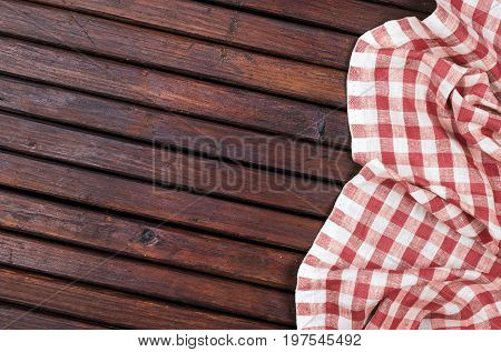Red checkered tablecloth on dark wooden table with, top view with copy space