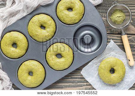 Freshly baked matcha banana donuts in baking dish horizontal top view