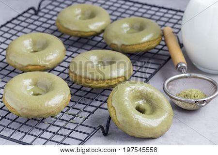 Freshly baked matcha banana donuts with matcha glaze on cooling rack horizontal