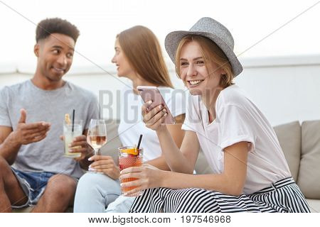 Friendly Youngsters Relaxing At Restaurant, Drinking Cocktails Or Wine, Communicating With Each Othe
