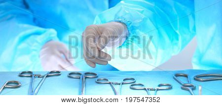 Close up of of surgeon's hands at work in operating theater toned in blue. Medical team performing operation.