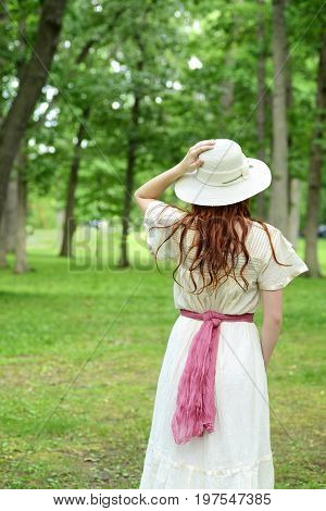 vintage woman holding her hat in park