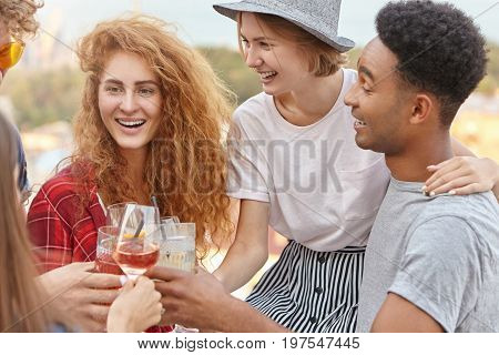Group Of Mixed Race Friends Raising Drinks For Cheers Celebration, Embracing Each Other, Celebrating