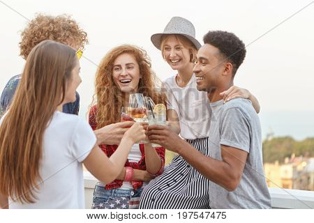 Party, Celebration, Rest And People Concept. Interracial Friends Clinking Drink Glasses With Happy E