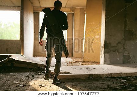 Athletic Man Walks Through The Ruins, With A Cover For A Gun For Weeping, Warm Rays Of Light In The