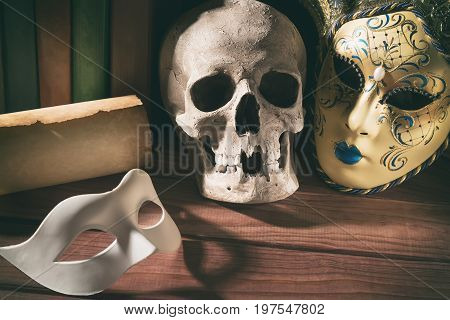Theater and drama concept. Human skull venetian masks with old scroll and books on wooden table.