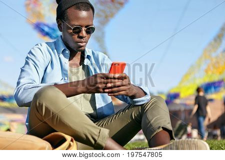 Restful Black Male Wearing Sunglasses, Hat, Shirt And Trousers Sitting At Green Grass Outside Using
