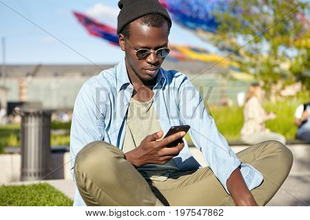 Fashion, Lifestyle And Technology Concept. Outdoor Shot Of Fashionable Guy Wearing Trendy Clothes An