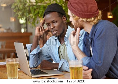 Two Mixed Race Friends Meeting Together At Cafeteria Sitting In Front Of Opened Laptop Watching Film