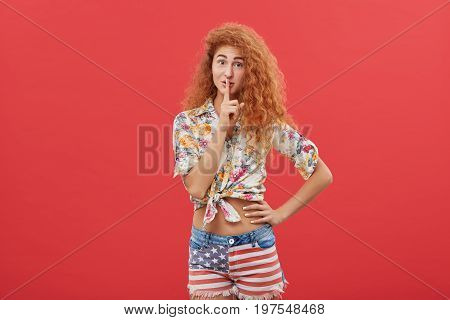 Attractive Ginger Female With Freckles Wearing Shirt And Shorts Holding Finger On Her Lips Asking To