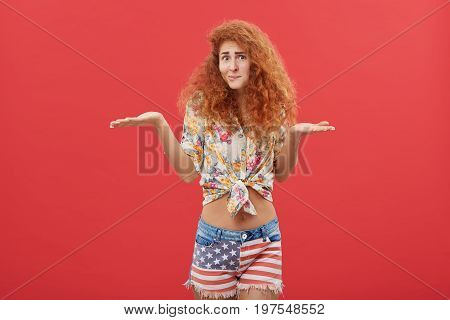 Clueless Young Red-haired Woman Wearing Casual Shirt And Shorts Shrugging Shoulders Having Doubts An