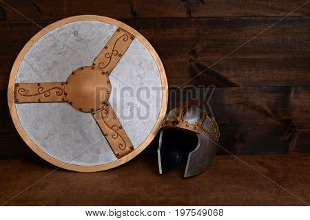 warrior helmet and shield on wood table