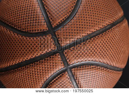 Old basketball ball on black background closeup. Active game, healthy lifestyle, streetball concept
