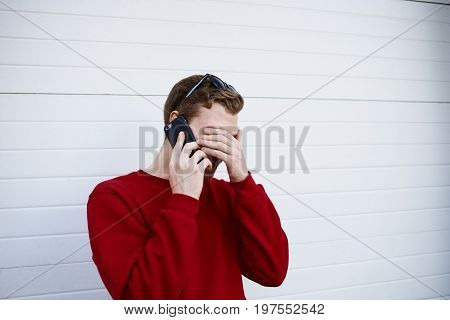 Bearded young Caucasian male in sweater having phone conversation with his friend making facepalm gesture while laughing at funny story or joke. Modern technology and communication concept