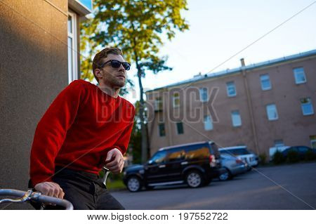 Urban portrait of confident bearded Caucasian hipster guy wearing red sweatshirt black jeans and sunglasses leaning on his retro bicycle relaxing after bike ride with empty street in background