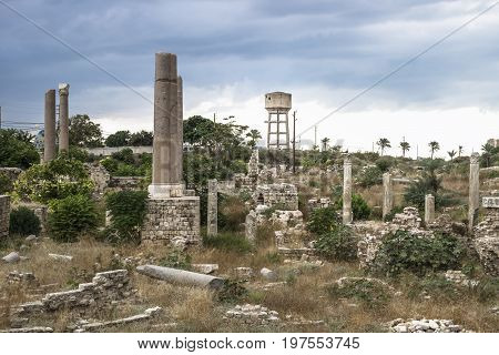 Ruins and watertower with dark dramatic cloudscape in Tyre, Sour, Lebanon
