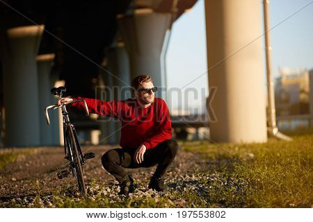 Handsome guy in trendy shades sitting in squatting posture on grass holding his fixed gear bicycle relaxing after long ride. People leisure hobby active healthy lifestyle and transportation