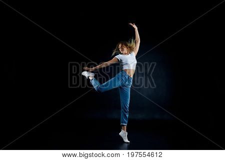 Picture of amazing agile talented young Caucasian female dancer wearing sneakers and sensible clothes demonstrating her skills in dance improvisation dancing with eyes closed feeling free