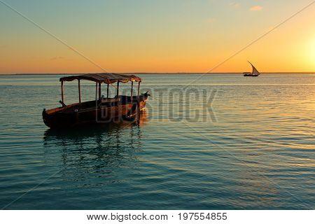 Wooden boat on water at sunset, Zanzibar island