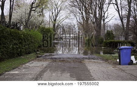 Landscape view of flood waters rising over a paved road in front of a gated property with trees foliage and a house partly submerged in the distance in the West Island of Montreal, Quebec on a bright overcast day in May.