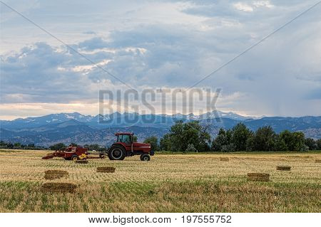 A scenic landscape view into the agriculture farming fields of Colorado with a tractor and harvesting of hay bales.