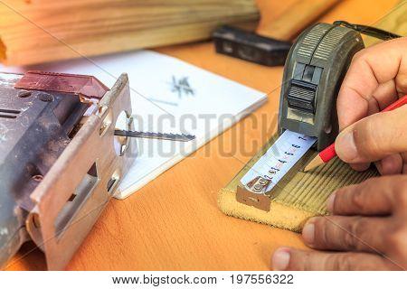 Carpenter taking action on a wooden slat