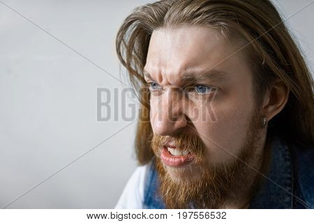 Close up studio portrait of angry mad young man with thick beard and long hairstyle frowning and clenching teeth his eyes full of anger and fury. Negative human emotions aggression rage and frenzy