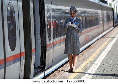MOSCOW/ RUSSIA - JUNE 30, 2017. The train conductor waiting for the passengers of the high speed electric train Sapsan between Moscow and Saint Petersburg. Moscow, Russia