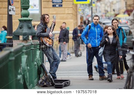 SAINT PETERSBURG/ RUSSIA - June 30, 2017. Street musician playing on the Italian bridge in the historic center of Saint Petersburg, Russia.