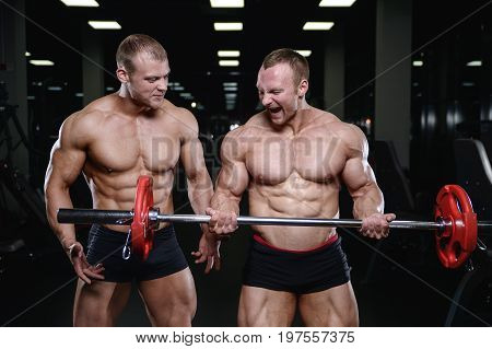 Two brutal strong athletic men pumping up muscles and train in gym workout bodybuilding on diet concept background - muscular bodybuilder handsome men doing exercises in gym naked torso