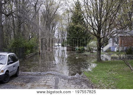 Landscape view of flood waters rising over a paved road with trees foliage and a house partly submerged in the West Island of Montreal, Quebec on a bright overcast day in May.