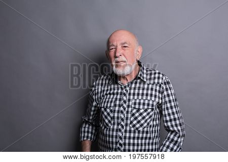 Mature man expressing disgust on face, grimacing on camera, gray studio background. Negative emotions