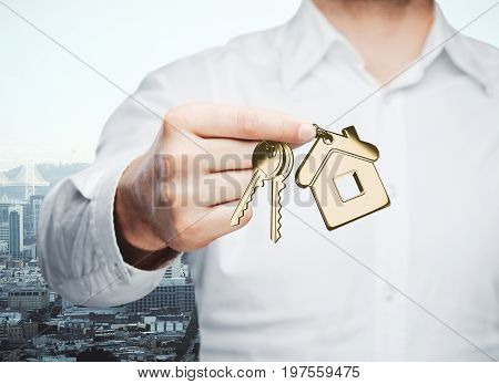 Businessman holding key with house keychain on city background. Real estate concept