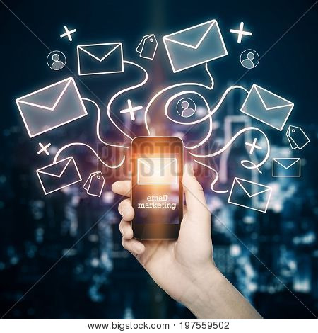 Hand holding mobile phone with abstract email network hologram on nigth city background. E-mail marketing concept