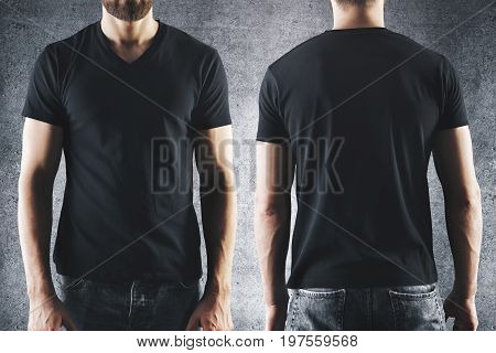 Shirt design and people concept. Close up of male in blank black t-shirt front and rear view. Clean empty mock up template for your design. Concrete background
