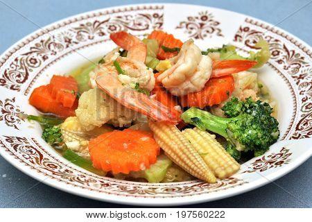Shrimp stir fry with vegetables carrots peas broccoli onions and garlic sauce